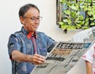 沖縄県知事選から一夜明け、当選を報じる新聞を広げる玉城デニー氏(1日午前、沖縄県沖縄市)