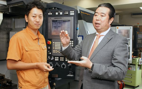 製品を手に技術者と語る日進工具・後藤弘治社長(右)(東京都品川区)