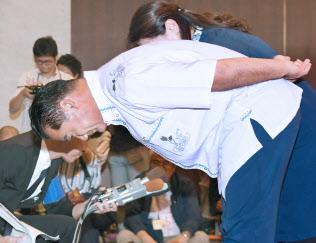 落選が決まり、支持者らに頭を下げる佐喜真淳氏(9月30日、那覇市)