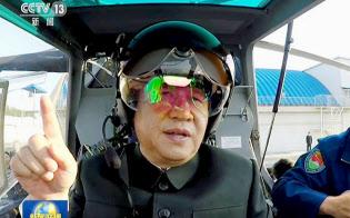 中国中央テレビが29日放映した、遼寧省の軍部隊でヘルメットをかぶり武装ヘリコプターの操縦席に着く習近平国家主席の映像=共同
