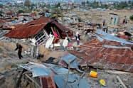 1日、地震で倒壊した家屋から荷物を運び出す住民=ロイター