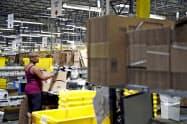年末商戦向けに短期で雇う10万人の最低賃金も引き上げる(アマゾンの物流施設)=AP