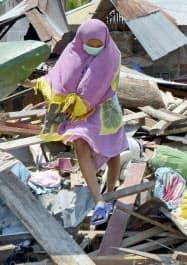 津波で壊れた自宅のがれきから生活用品を探す住民(3日、インドネシア・スラウェシ島)=共同