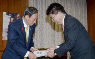 加藤前拉致問題担当相(右)から引き継ぎ書を受け取る菅官房長官(4日午後、東京・永田町)