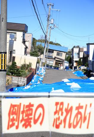 家屋や電柱が傾いたままの住宅街(4日、札幌市清田区)