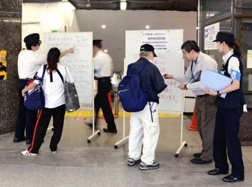 京成上野駅前で利用客の対応に追われる職員ら(5日午後、東京都台東区)=共同