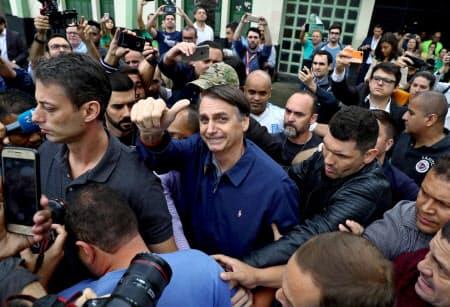 7日、投票を終え支持者らに応えるボルソナロ氏(写真中央、リオデジャネイロ)=ロイター