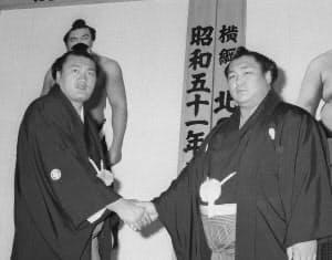 1976年5月、横綱北の湖(右)と握手を交わす輪島=共同