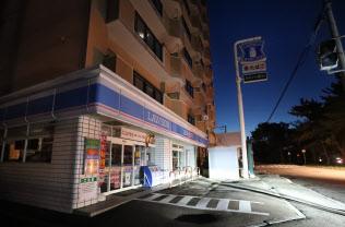 停電し、明かりが消えたコンビニエンスストアとマンション(9月6日未明、北海道函館市)