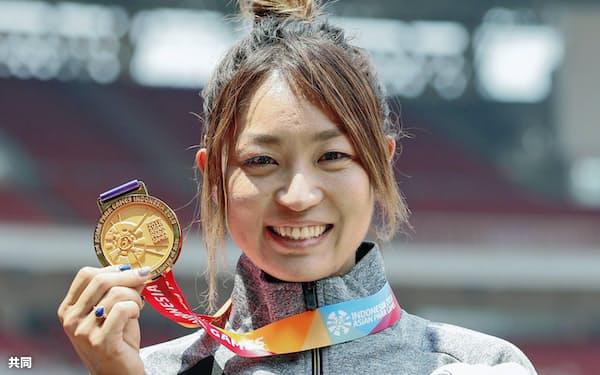女子走り幅跳び(義足など)で金メダルを獲得し、笑顔の中西麻耶(9日、ジャカルタ)=共同