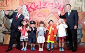 「キッザニア東京」で子どもたちと写真に納まるKDDIの高橋誠社長(右端)とKCJグループの住谷栄之資社長兼CEO(左端)=10日午前、東京都江東区
