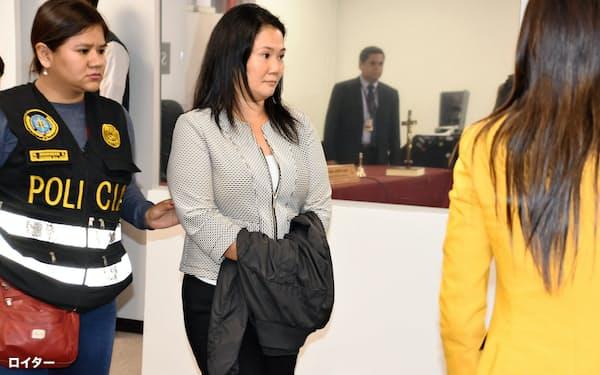 10日、身柄を拘束されたケイコ・フジモリ容疑者(写真中央、リマ)=ロイター