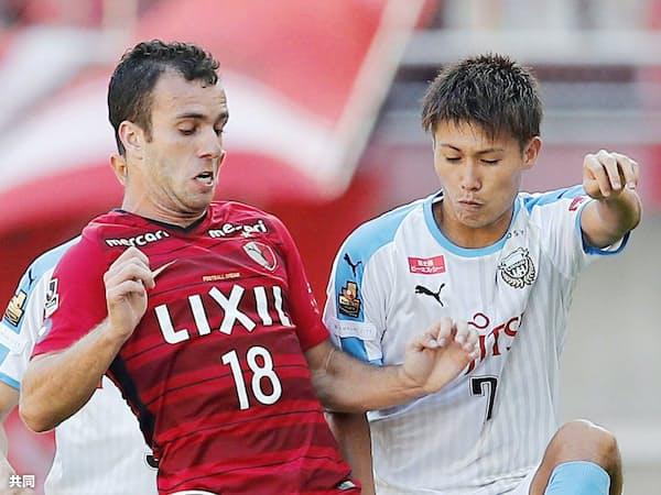 Jリーグは日本サッカーを強くすることも大命題にしている(写真は鹿島・セルジーニョ=左=と競り合う川崎・車屋)=共同
