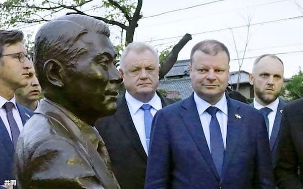 杉原千畝の母校、愛知県立瑞陵高校を訪れ、功績を紹介する新施設で等身大銅像を見るリトアニアのスクバルネリス首相(右から2人目)=11日午後、名古屋市(共同)