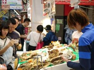 カキをさばく様子をスマートフォンなどで撮影する訪日客(大阪市の黒門市場)