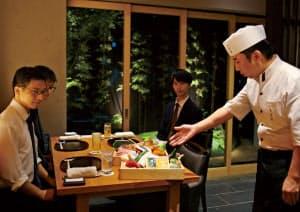 客に食材について説明する斗米庵の料理人(右)。錦の食材調達力のアピールに一役買う