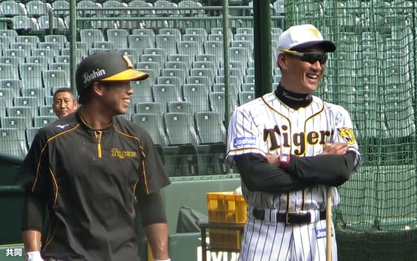 練習中に笑顔を見せる阪神の金本監督。左は梅野(12日、甲子園)=共同