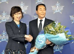 南場智子オーナー(左)から花束を受け取るDeNAの高田GM(12日、横浜市内の球団事務所)=共同