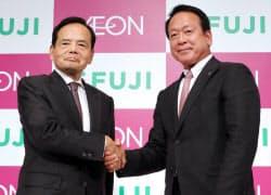 記者会見で握手するイオンの岡田社長(左)とフジの尾崎会長兼CEO(12日、東京都千代田区)