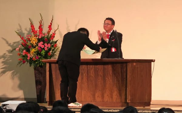 顕彰施設の名称を考案した生徒を表彰する愛知県の大村秀章知事(右)(12日、名古屋市瑞穂区の県立瑞陵高校)