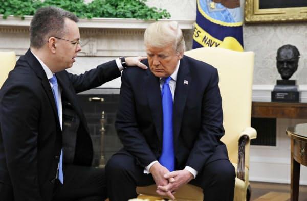ホワイトハウスで、解放されたブランソン牧師(左)とともに祈るトランプ米大統領(13日、ワシントン)=AP