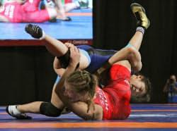 レスリング女子57キロ級決勝で攻める尾崎野乃香(上)。金メダルを獲得した(13日、ブエノスアイレス)=共同