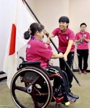 ジャカルタ・アジアパラ大会日本選手団の解団式で、大前千代子団長(左)に団旗を手渡す陸上女子の前川楓(14日、ジャカルタ)=JPC提供・共同