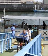 渡し船から自転車を押して下りる利用客(大阪市)=共同
