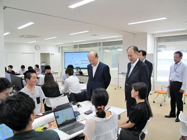 ワークショップ中の学生を激励する石井知事(中央左)と鎌田総長(同右)