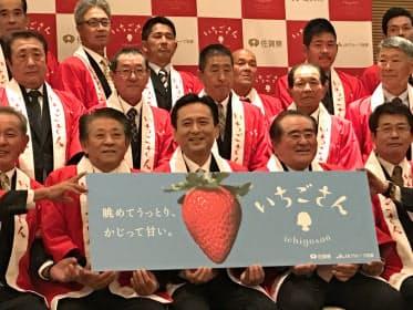 ロゴマーク入りのパネルを持ち新品種をアピールする佐賀県の山口祥義知事(16日、佐賀市内)