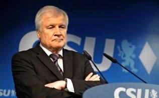 15日、記者会見で腕組みするキリスト教社会同盟(CSU)党首のゼーホーファー内相=AP