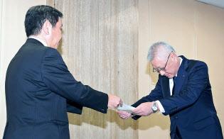 国交省の石田優住宅局長(左)から指示書を受け取るKYBの中島康輔会長兼社長(16日午後、国交省)