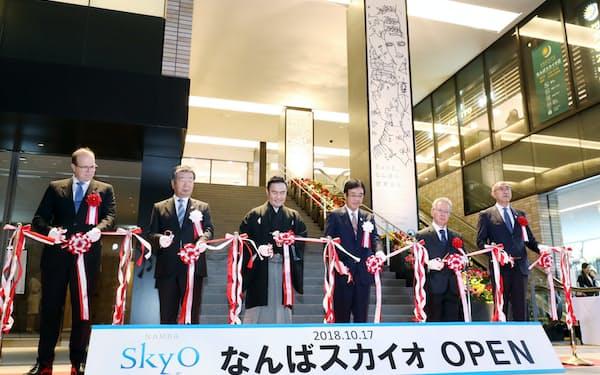「なんばスカイオ」の開業記念式典でテープカットする南海電鉄の遠北社長兼CEO(右から3人目)ら(17日午前、大阪市中央区)