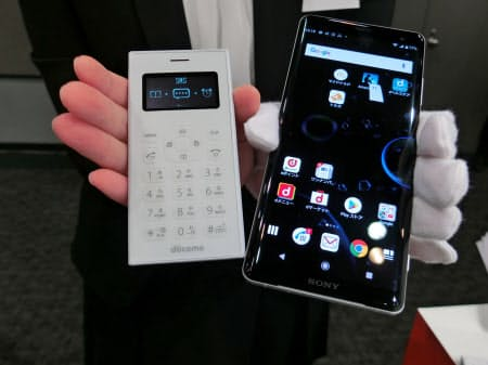 ドコモのワンナンバーフォン(左)は、スマホの「子機」として提案する