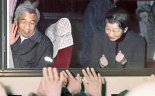 阪神大震災の被災者を見舞い、バスの中から見送りの人たちに手を振る天皇陛下と「頑張って」とこぶしを握る皇后さま=1995年1月、兵庫県北淡町(現淡路市)=共同
