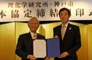 基本協定書を手にする理研の松本理事長(左)と神戸市の久元市長(神戸市)