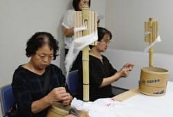 結城紬の材料となる、糸の紡ぎを体験する担い手育成説明会の参加者(茨城県筑西市)=共同