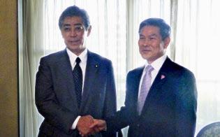 韓国の鄭景斗国防相(右)と会談し、握手を交わす岩屋防衛相(20日、シンガポール)=共同