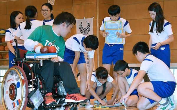 ボッチャ競技を活用した算数の授業に参加する小学生。左手前は広瀬隆喜選手(22日午前、東京都渋谷区の代々木山谷小)