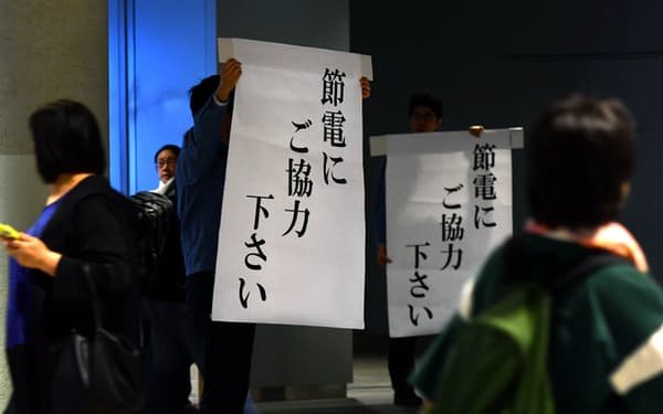 節電のため暗くなった地下通路で市民に節電を呼びかける北海道電力の社員(10日午後、札幌市中央区)