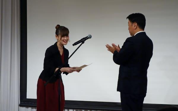 徳島商議所の中村太一会頭から「とくしまクチコミ大使」を委嘱されたシンガーソングライターの福富さん(左、22日、徳島市)
