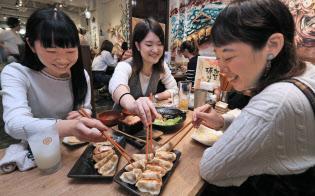 看板メニューの「肉汁焼餃子」を食べる女性客(ダンダダン酒場新宿店)