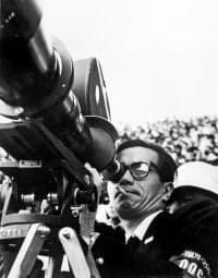 1964年、記録映画「東京オリンピック」の撮影でカメラのファインダーをのぞく市川崑監督(C)公益財団法人 日本オリンピック委員会