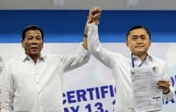 側近の上院選出馬の手続きに同行したドゥテルテ大統領(左)(15日、マニラ)=AP