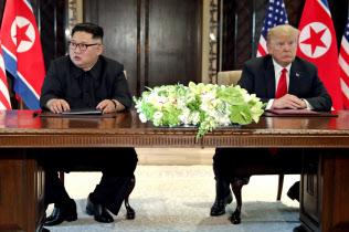 6月12日、初の首脳会談を行ったトランプ大統領(右)と金正恩委員長(シンガポール)=ロイター
