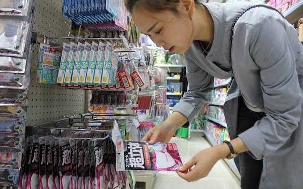 ユニ・チャームの「超立体マスク」を買おうとしている中国人女性。訪日旅行後に日本の日用品を買う人が増えている(10月、遼寧省大連)