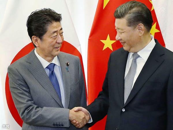 握手する中国の習近平(シー・ジンピン)国家主席(右)と安倍首相(9月12日、ロシア・ウラジオストク)=共同
