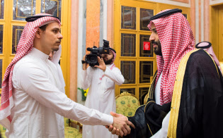 23日、ムハンマド皇太子(右)と握手を交わすサラー・カショギ氏。表情はこわばっていた(サウジ王室提供)=ロイター