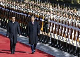 北京の人民大会堂で歓迎式典に臨む安倍首相(手前右)と中国の李克強首相(26日)=共同