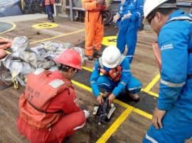 墜落現場近くで残骸を調べる関係者(29日)=ロイター・アンタラ通信